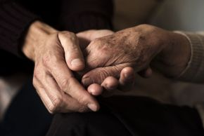 A person holding the hand of an elderly woman using both hands. Signifies a coping strategy.