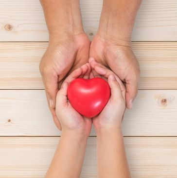 Two pair of hands holding each other with a red heart.