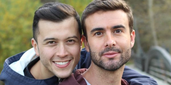 Happy gay couple smiling and embracing.