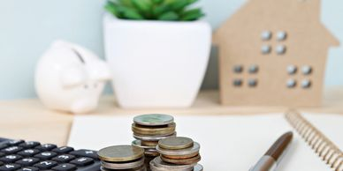 Coins in 3 stacks, next to a keyboard with a plant and paper cutout of a home in the background. Depicting financial abuse