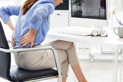 Lower back pain treated with physiotherapy at work by the Home Physios