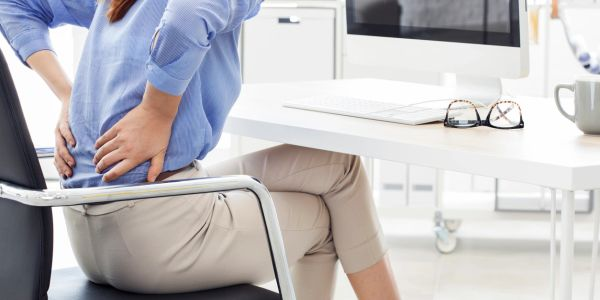 A woman grasping back hunched over with back pain from working from home.
