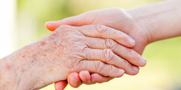 an elderly womans hand shaking a young nursing home workers hand