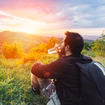A young hiker takes a break on top of a mountain to see a beautiful sunset while hydrating with a fresh bottle of bottled water