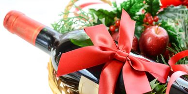 Gift basket with red accents - there is a partial bottle of wine with a red bow and green wreath