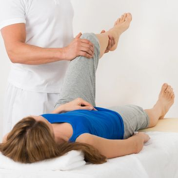 Person receiving active stretching techniques lying on back with left leg bent at right angle.