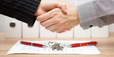 Shaking hands over signed agreement