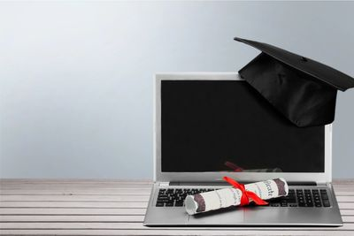 Laptop with diploma and cap on it.