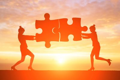 2 women in high heels holding large puzzle pieces together as if to be working together