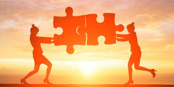Picture of two people with puzzle piece coming together.