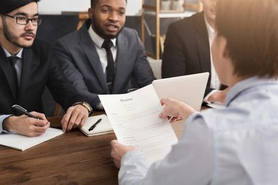 Young person with their resume in an interview with a recruitment panel