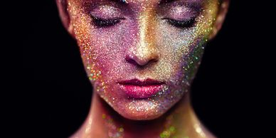 The face of a lady with glitter on. Her eyes are closed. Signifies the importance of identity.