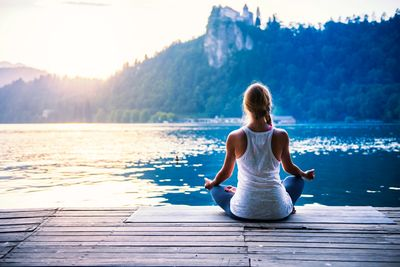 woman meditating along lake