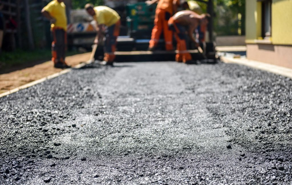 Contractors laying asphalt for a driveway