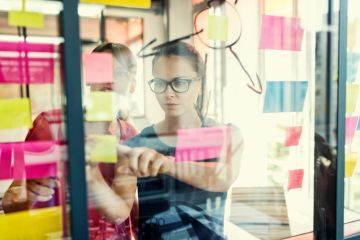 Outsourced Marketing Manager - two women looking at post-its on the glass