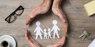 A pair of hands circling a paper cut out of a family