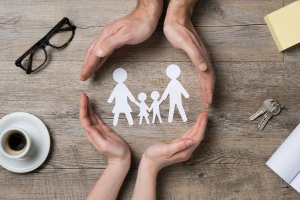 Hands around a paper cutout family. Lets support VOGM families.