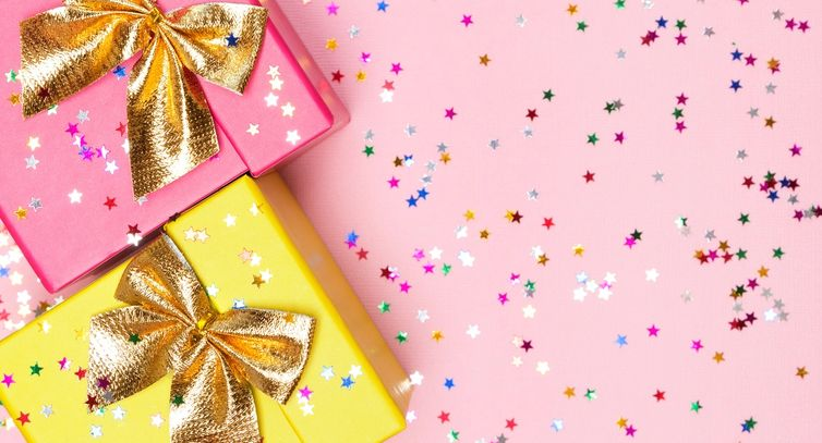 Pink gift box with gold ribbon and yellow gift box with gold ribbon on pink background with confetti
