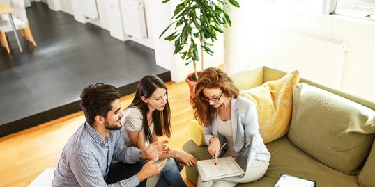 Insurance agent assisting young couple with purchasing home , auto and life insurance