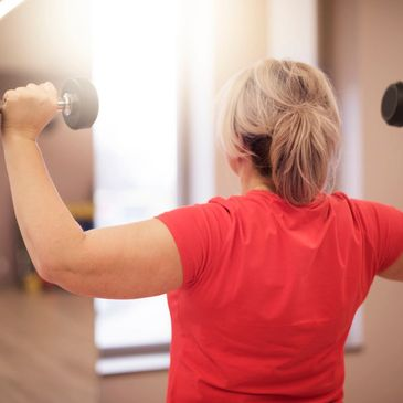 woman doing shoulder press with dumbbells