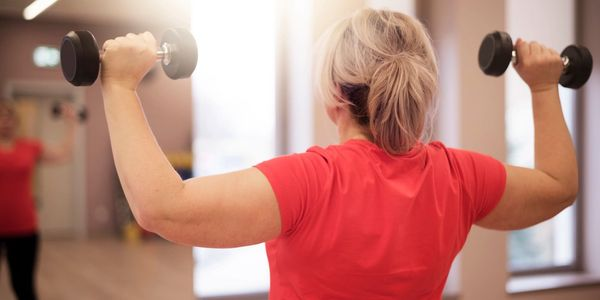 Middle aged woman performing arm exercises with weights