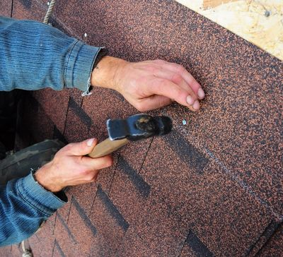 A worker installing roofing nails into roofing shingles by hand.