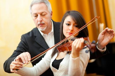 Professional Instructor teaching student how to hold a bow and play violin
