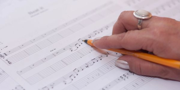 Picture of a hand writing music.