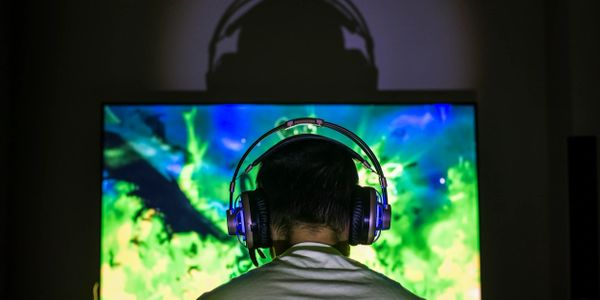 A man wearing a gaming headset in front of his monitor.