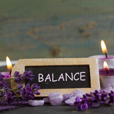Word Balance on chalkboard surrounded by lavender blooms & stones w/purple tea lights in background
