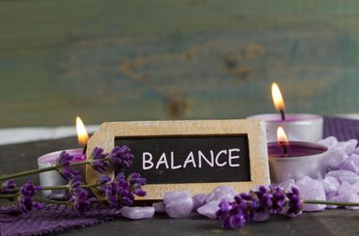 Sign that says Balance surrounded by purple tealight candles, flower sprigs, and rocks.