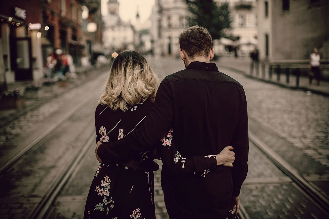 Couple walking down a city street on a date together.