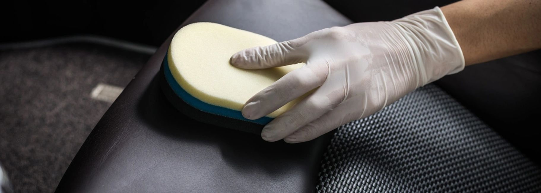 A gloved hand is using a brush to remove dirt from a leather car seat.