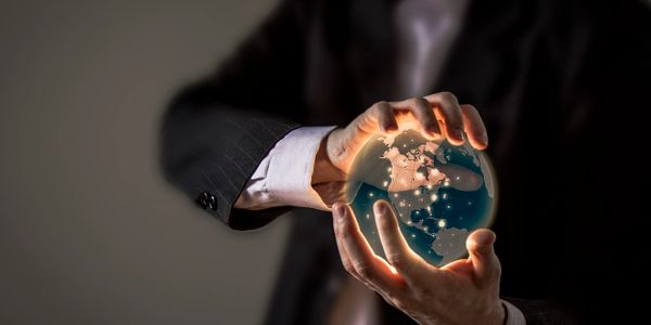 Man in suit holding world globe in his hands