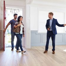 A Real Estate Agent showing a couple around a new home.