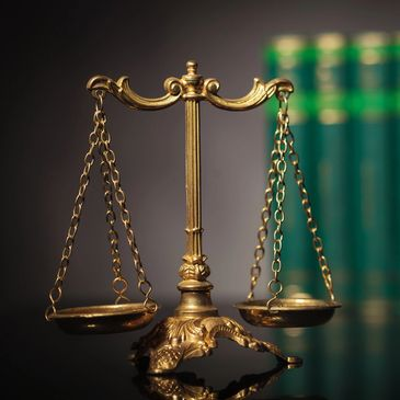 The scales of justice on a table with books in the background.