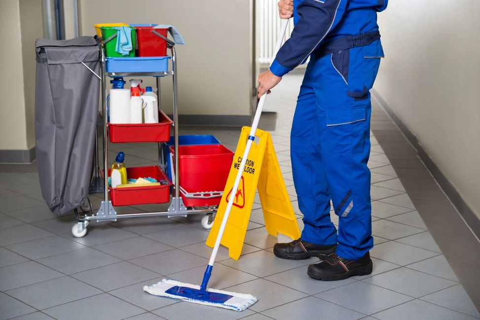 A man using a mop to clean the floor
