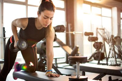 Woman in a gym doing triceps extensions with a dumbell