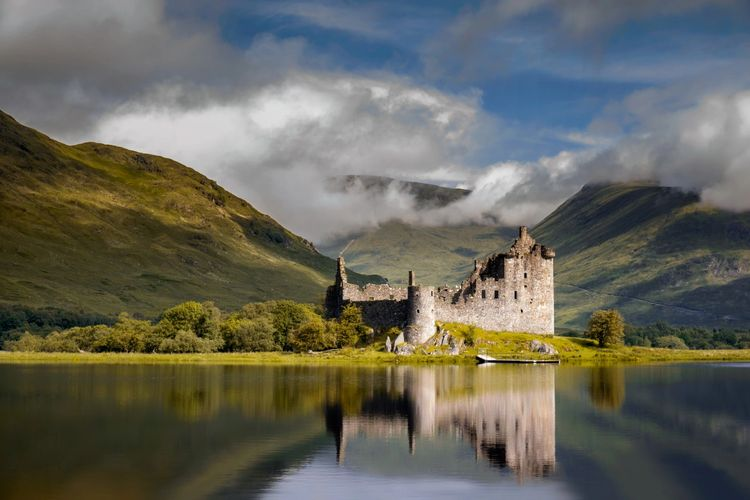 Scottish loch-side castle with backdrop of mountains and whispy white clouds