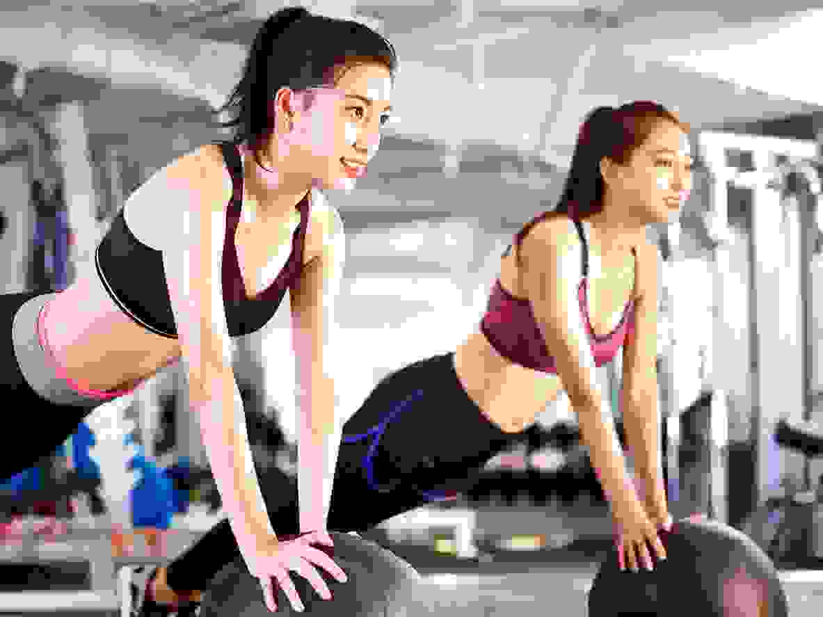 2 asian women exercising with a big ball for exercise and fitness