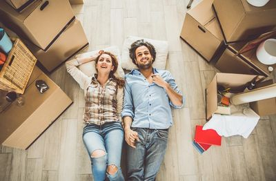 Man and woman lying on floor surrounded by moving boxes