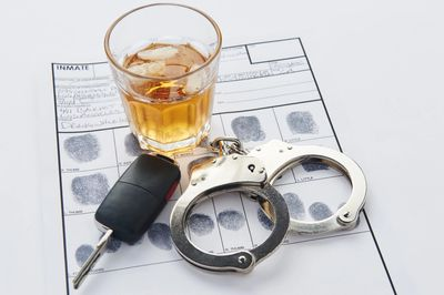 Glass of alcohol keys and handcuffs on top of fingerprint card denoting being arrested for dwi.