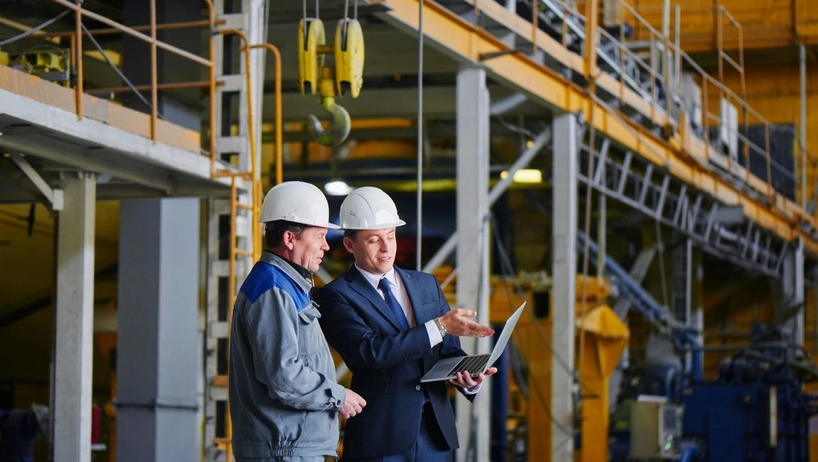 two men in hardhats looking at a laptop in industrial setting