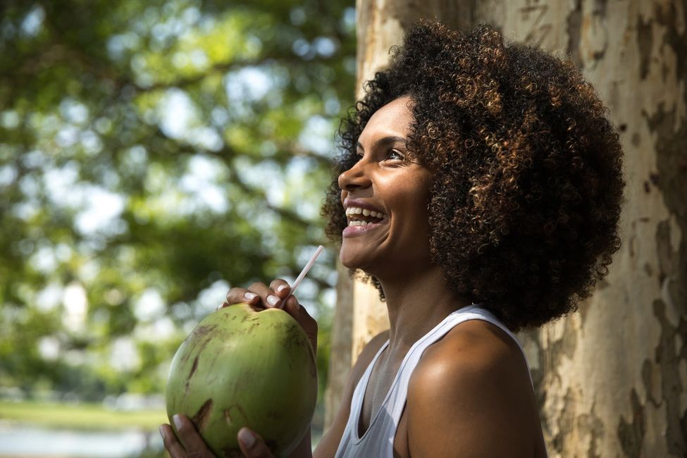 Beautiful woman drinking the milk of a ripe and fresh picked coconut from the Jungles of Costa Rica.