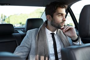 Executive wearing a suit in back seat of chauffeur driven car on the way to a Business meeting