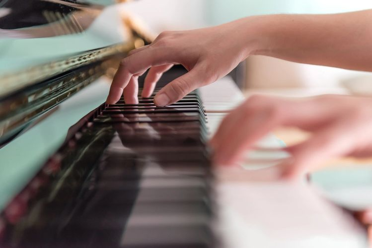 Hands on a piano keyboard during piano lessons