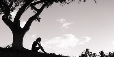 Depressed woman sitting under a tree