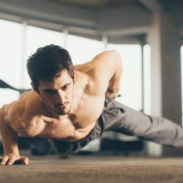 Weekend Pass -  a fit man wearing grey trousers is doing a one arm push up