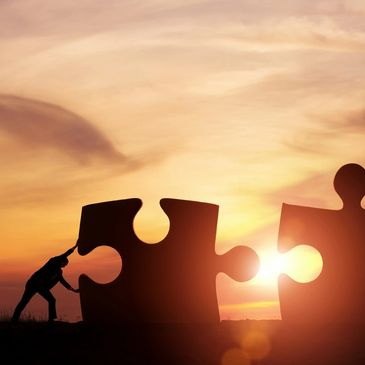 Two people moving large jigsaw pieces closer together under a sunset.