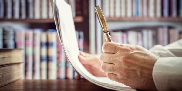 Detail of man's hands examining a document with a magnifying glass with law books in the background